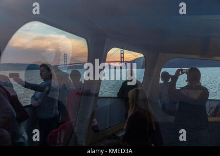 Passengers on ferry from Sausalito to San Francisco and Golden Gate Bridge in background,California,USA - Stock Photo