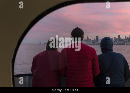 rear view of three passengers on ferry from Sausalito to San Francisco looking at view of city,California,USA - Stock Photo
