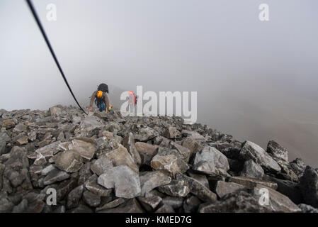 A group of climbers holding a rope on a rocky section while hikking up at the Nevado de Toluca volcano in Estado - Stock Photo
