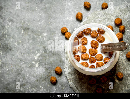 Fitness food. Chocolate cereal with milk. On the stone table. - Stock Photo