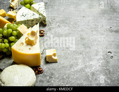 Different cheese , grapes and nuts. On the stone table. - Stock Photo