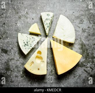 Various pieces of cheese around. On the stone table. - Stock Photo