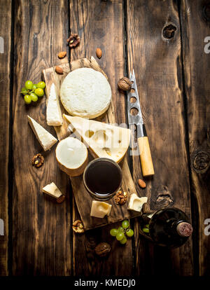 Red wine with chunks of cheese and nuts. On a wooden table. - Stock Photo