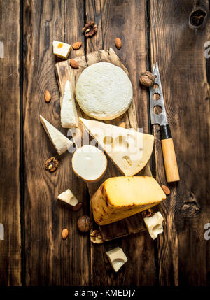 Pieces of cheese with nuts on a Board with a knife. On a wooden table. - Stock Photo