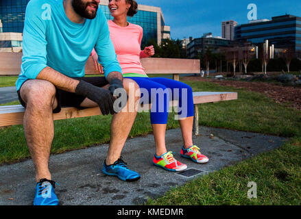 Two runners sit on a bench at dusk after a run in Seattle, WA. - Stock Photo