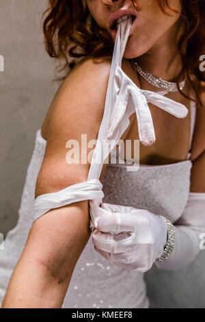 Female drug addict applying tourniquet, Oakland, California, USA - Stock Photo