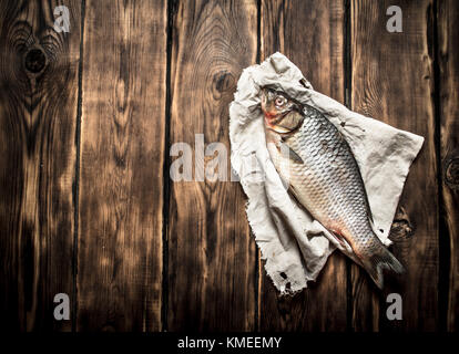 Fresh fish on the old fabric. On wooden background. - Stock Photo