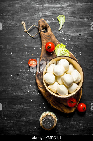 Mozzarella in a bowl with the tomatoes and herbs. On a black wooden background. - Stock Photo
