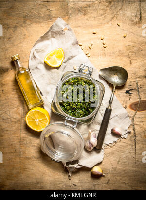 Italian pesto with lemon, pine nuts and other ingredients. On a wooden table - Stock Photo
