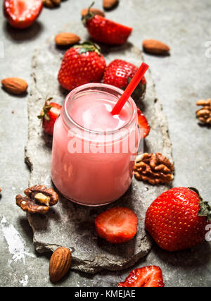Strawberry smoothie with milk and nuts. On the stone table. - Stock Photo