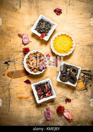 Different types of dried tea in the cups . On wooden background. - Stock Photo