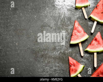 Slices of watermelon on wooden sticks. On the stone table. - Stock Photo