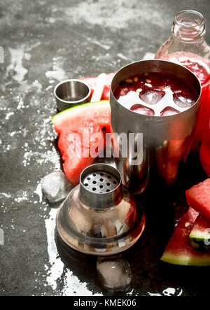 Watermelon cocktail with ice in a shaker. On the stone table. - Stock Photo