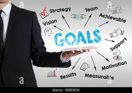 Goals concept. Chart with keywords and icons. Man holding a tablet computer - Stock Photo