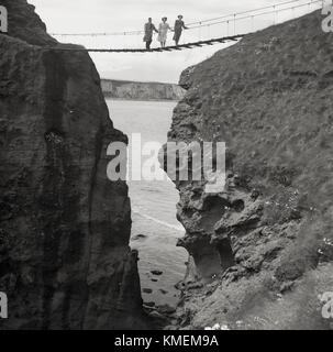 1950s, historical, a man and two ladies pose for a picture standing on the famous Carrick-a-Rede rope bridge, Co - Stock Photo