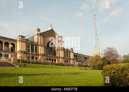 Alexandra Palace, south elevation, with Rose window and iconic TV mast/ antenna, in sunshine, blue skies, with grass - Stock Photo