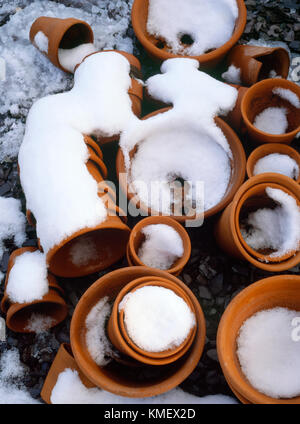 Stacks of small, mainly hand made, terracotta flower pots left out over winter. 23cm - 10cm diameter. - Stock Photo