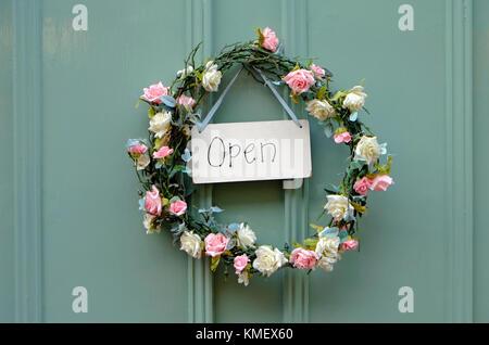 rose wreath and open sign on shop door, norfolk, england - Stock Photo
