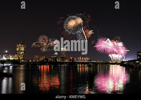 Fireworks over Boston on 4th of July celebration. City skyline and lights reflected on Charles River. - Stock Photo
