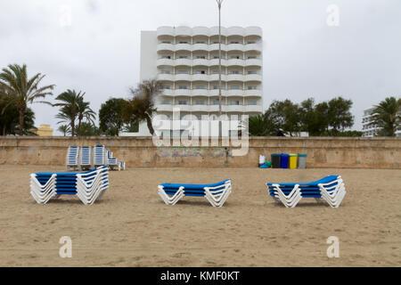 empty sunbeds, out of season, on beach on a rainy day - Stock Photo