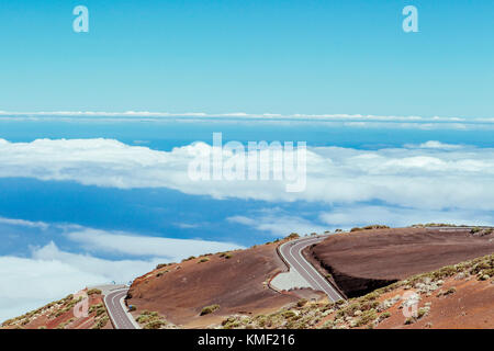 Cyclists pedaling on winding mountain road above clouds,Teide National Park,Tenerife,Canary Islands,Spain - Stock Photo