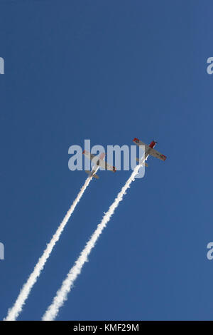 Two propeller airplanes flying together with smoke trail in deep blue sky