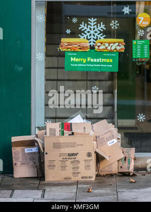 Merry Feastmas at Subway in Preston with cardboard boxes awaiting street collection, UK - Stock Photo