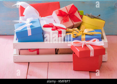 Gifting theme image with a bunch of colorfully wrapped presents, in a white wooden crater, on a pink table and a - Stock Photo