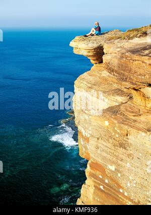 Young woman sitting on cliffs of Dunnet Head above Pentland Firth on north coast of Caithness in Highland region - Stock Photo