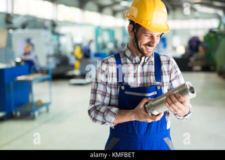 Portrait of an metal engineer working at factory - Stock Photo