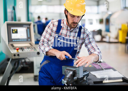 industrial factory employee working in metal manufacturing industry - Stock Photo