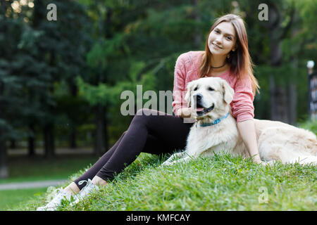Photo of woman and dog sitting on lawn - Stock Photo