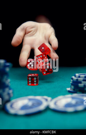 Photo of man throwing red dices on table with chips in casino - Stock Photo