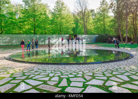 Roma Holocaust Berlin, visitors look at the reflecting pool in the Gypsy and Sinti Holocaust Memorial in the Tiergarten - Stock Photo