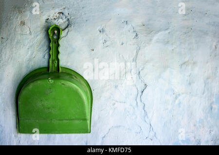 Green colored Dustpan hanging on the wall.Concept of cleanliness and neatness. - Stock Photo