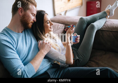 Romantic couple eating ice cream together and watching tv - Stock Photo