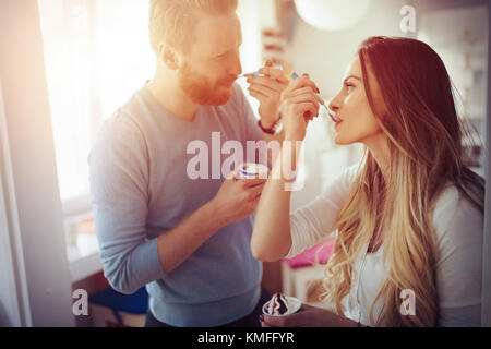 Couple having fun and laughing at home while eating ice cream - Stock Photo