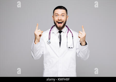 Portrait of a happy excited male doctor dressed in uniform pointing two fingers up and looking at camera over white - Stock Photo
