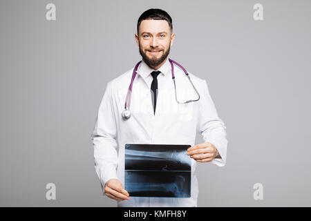 Portrait of a happy young male doctor with stethoscope dressed in uniform pointing finger at x-ray photograph isolated - Stock Photo