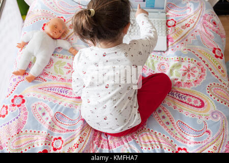 Little girl sitting in bed and playing online games with laptop computer. She is touching the screen - Stock Photo