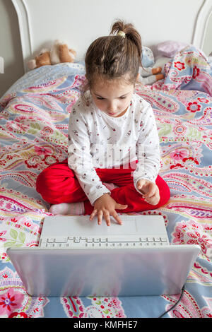 Little girl sitting in bed and playing online games with laptop computer - Stock Photo