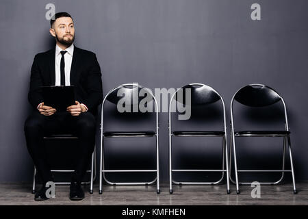 Confident job applicant reads resume while sitting on chair in row in office and waiting his turn on interview. - Stock Photo