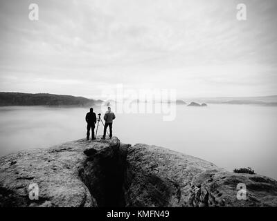Two warm coat photographers with tripod shoot pictures of autumnal landscape below mountain.  Rainy misty day in - Stock Photo