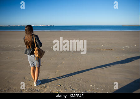 A woman admires the sea. She stands on the wet sand and stares into the distance. Blue sea, blue sky. - Stock Photo