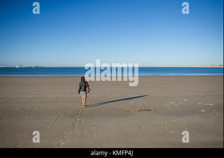 A woman admires the sea. She walks along the wet sand and looks into the distance. Blue sea, blue sky. - Stock Photo