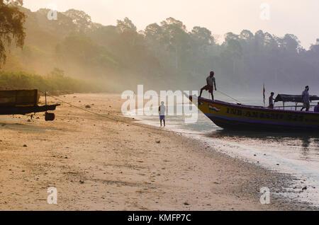 LONG ISLAND, ANDAMAN, INDIA - 23 MAR 2015: Fishermen drag their boat back to shore, at dawn, after a fishing trip - Stock Photo