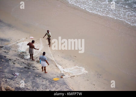 VARKALA, INDIA - circa FEBRUARY 2017: Three fishermen unfold and clean a fishing net after they returned to the - Stock Photo
