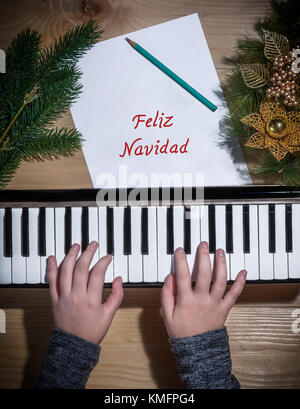 Feliz Navidad - Young hands of a girl playing on a keyboard with Christmas decorations on a wooden table - Stock Photo