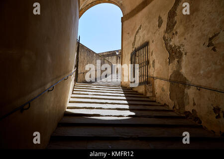 An ancient stone staircase with an arch and an open metal gate in a clear sunny day. Florence, Italy - Stock Photo