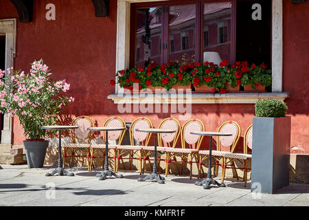 A nice European vintage summer cafe with small tables and wicker chairs, a facade decorated with flowers on a sunny - Stock Photo